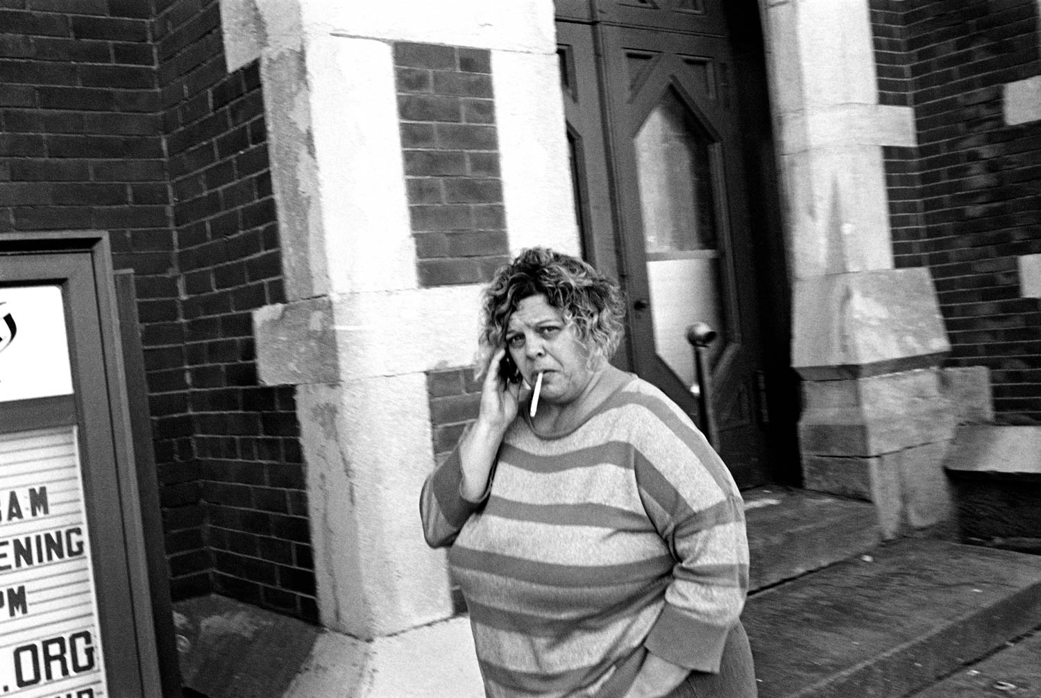 A black and white street photography of a woman talking on her cell phone and smoking on the streets of Binghamton, NY.