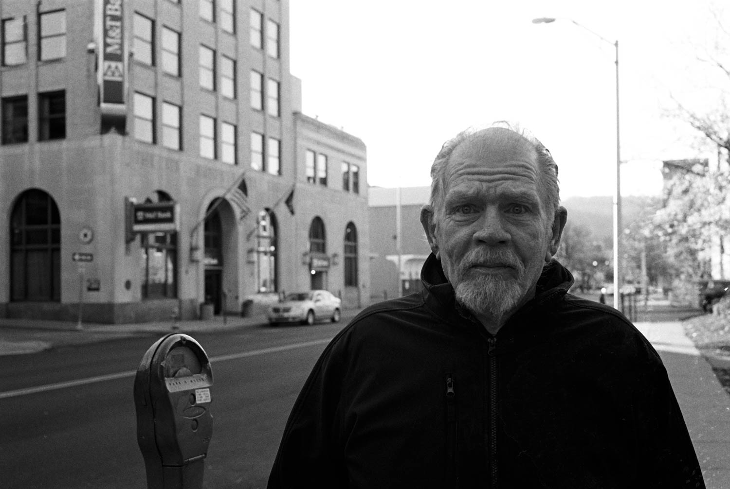 A black and white street portrait of a man standing on the sidewalk in Binghamton, NY
