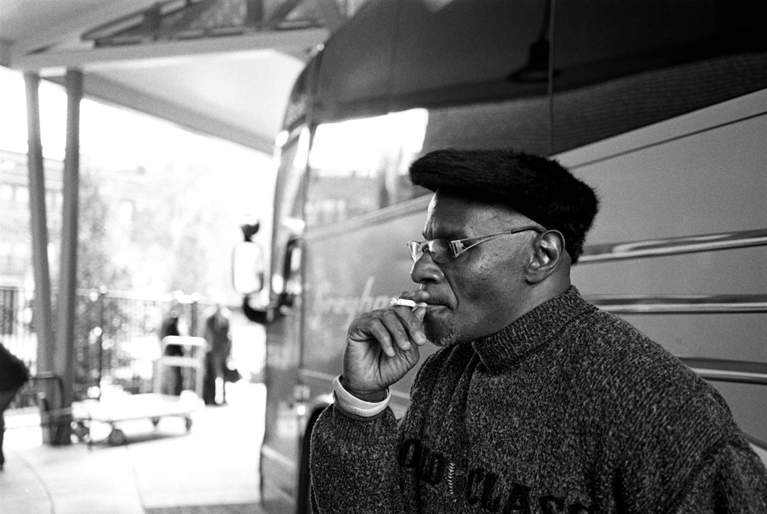 A black and white street photograph of a man smoking a cigarette while leaning against a bus in Binghamton, NY