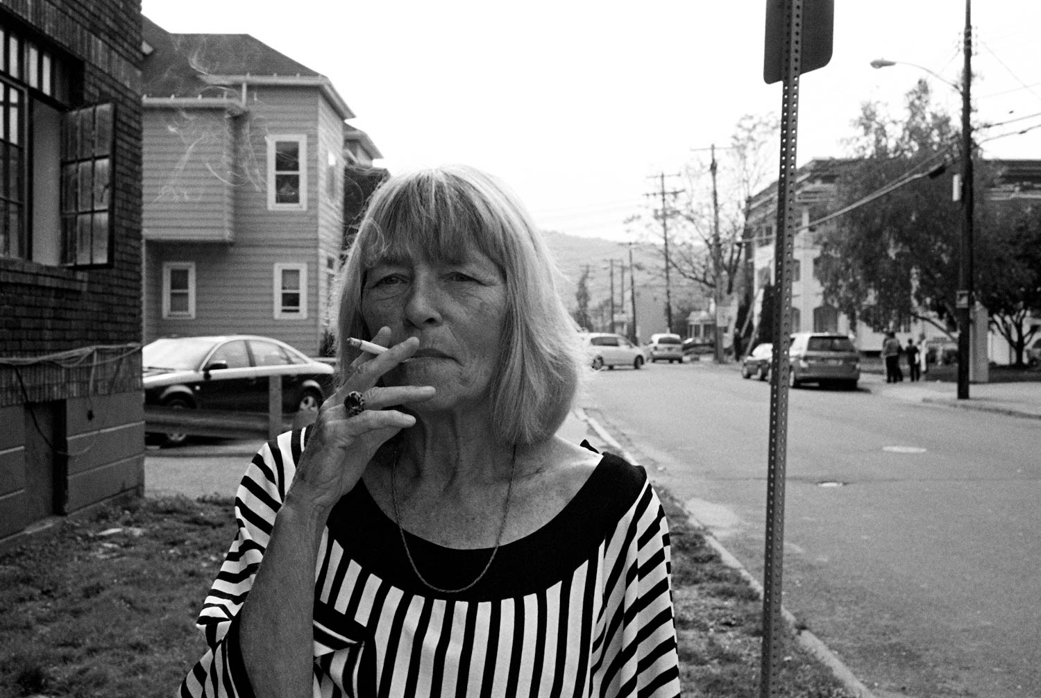 Black and white street photograph of an older woman in a vertical stripe shirt smoking a cigarette in Binghamton, NY.