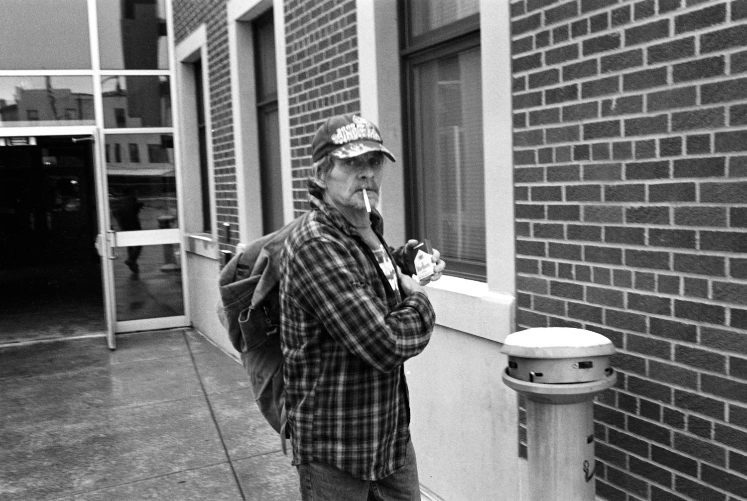 A black and white picture of a man putting a carton of cigarettes back into a flannel shirt pocket while walking out of the B.C. Junction in Binghamton, NY.