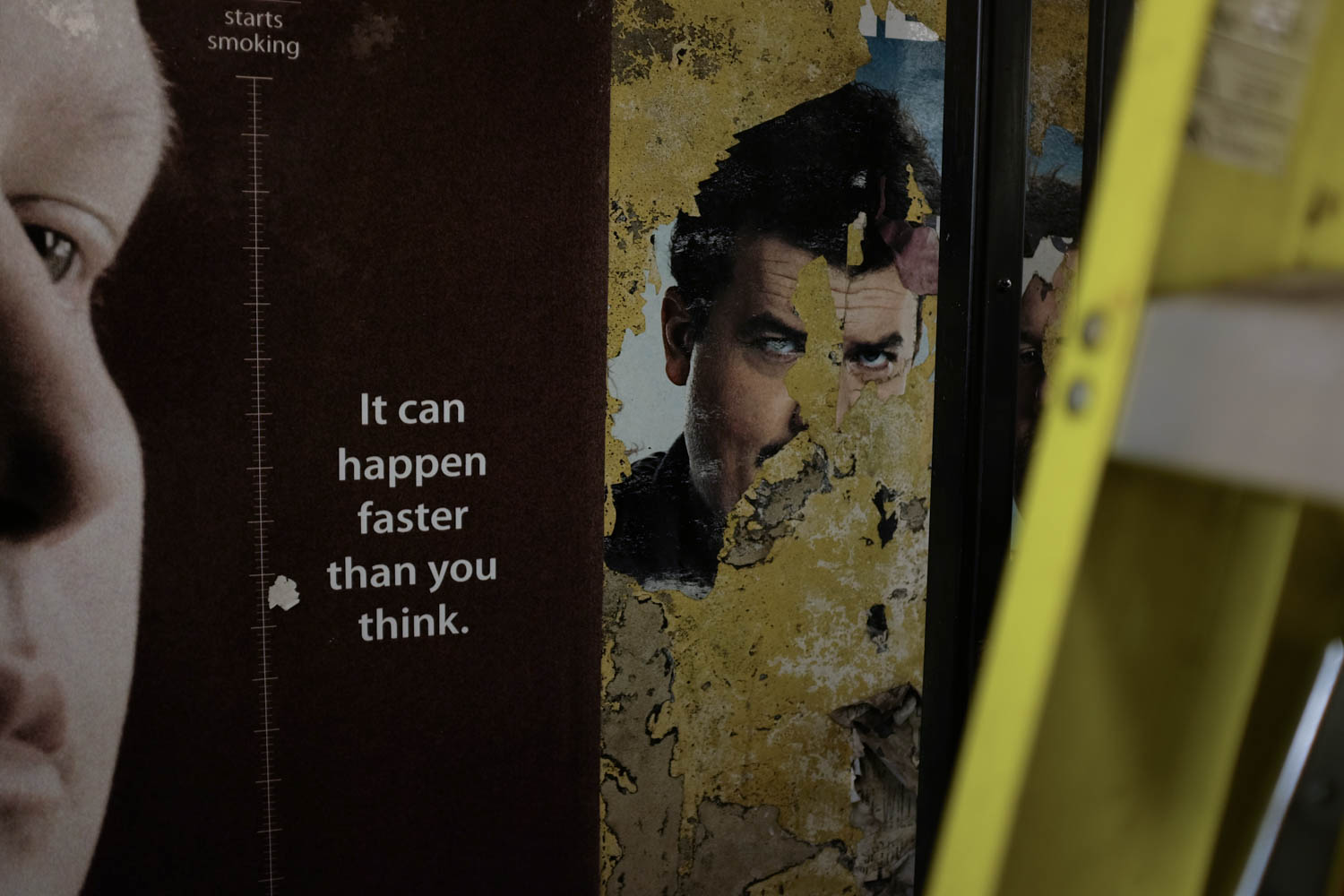 "A photograph of the text ""It can happen faster than you think"" next to the chipped away picture of a face on an adjacent poster."