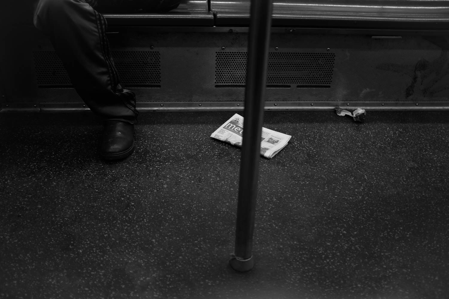 A black and white photograph of a newspaper on the floor of a subway car.