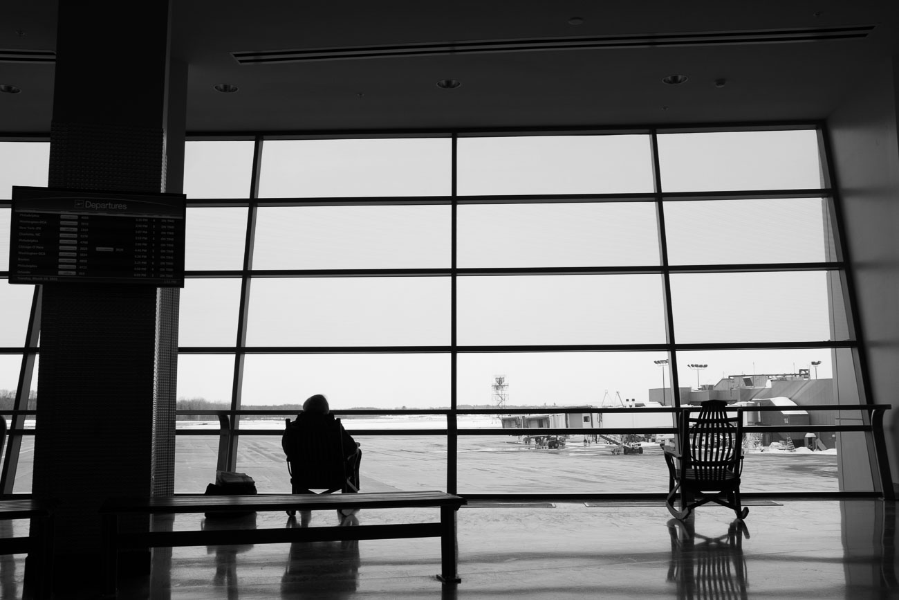 Black and white photo of a man sitting in a rocking chair in front of the large windows of the Syracuse International Airport.